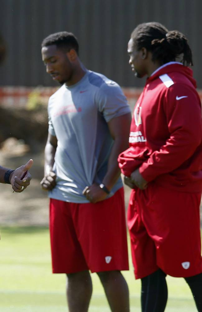 From left to right, former Olympic champion and Arizona Cardinals new assistant strength and conditioning coach Roger Kingdom,  instructs Cardinals players Stepfan Taylor, Robert Hughes and Jonathan Dwyer during the first phase of the voluntary offseason training program at the NFL football team's training facility on Thursday, April 24, 2014, in Tempe, Ariz