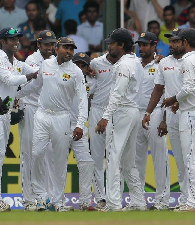 Sri Lanka team members greet Mahela Jayawardene, fourth left, as they walk in to field during the fourth day of the second test cricket match against Pakistan in Colombo, Sri Lanka, Sunday, Aug.17, 2014. Jayawardene is playing his final test