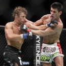 Urijah Faber, left, trades punches with Dominick Cruz during the first round of their UFC bantamweight mixed martial arts title match, Saturday, July 2, 2011 at The MGM Grand Garden Arena in Las Vegas. Cruz won by unanimous decision. (AP Photo/Eric Jamison)