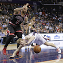 Charlotte Bobcats' Cody Zeller, front, loses the ball as he falls in front of Chicago Bulls' Carlos Boozer during the first half of an NBA basketball game in Charlotte, N.C., Wednesday, April 16, 2014 The Associated Press