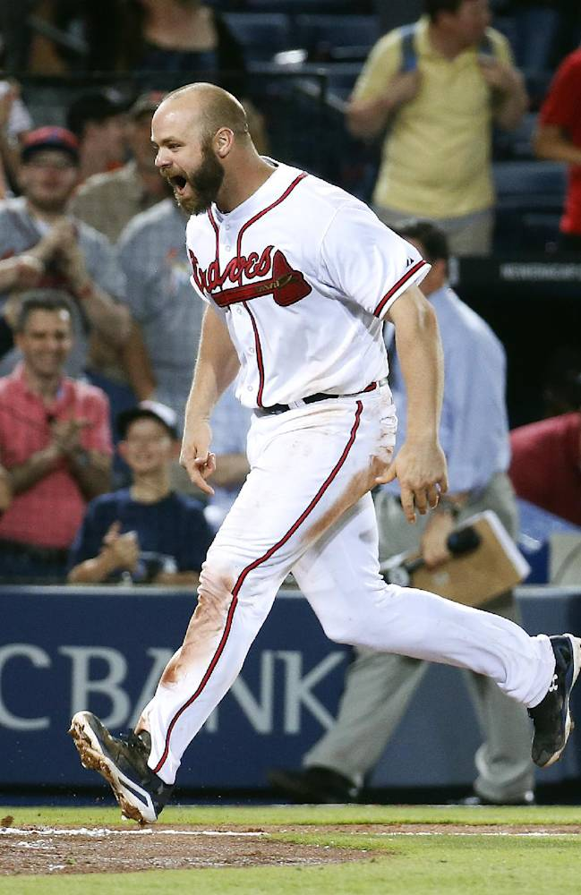 Atlanta Braves catcher Evan Gattis (24) rounds the bases after hitting  a two-run home run in the 10th inning of a baseball game against the Miami Marlins Monday, April 21, 2014 in Atlanta.  The homer gave the Braves a 4-2 victory