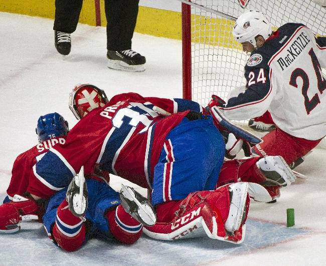 Columbus Blue Jackets' Derek MacKenzie, right, scores against Montreal Canadiens goaltender Carey Price, center, as Canadiens' P.K. Subban defends during the first period of an NHL hockey game in Montreal, Thursday, March 20, 2014