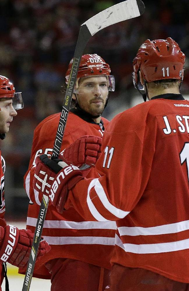 Carolina Hurricanes' Patrick Dwyer (39), Ron Hainsey (65), Jordan Staal (11) and Jay Harrison (44) celebrate Dwyer's goal against the Buffalo Sabres during the second period of an NHL preseason hockey game on Friday, Sept. 27, 2013, in Raleigh, N.C. Carolina won 1-0
