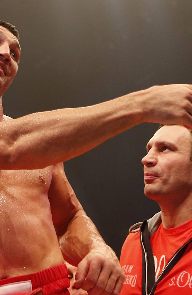IBF, WBA, WBO and IBO champion Wladimir Klitschko from Ukraine is watched by his brother Vitali, right, as he celebrates winning the heavyweight world title bout against his Australian challenger Alex Leapai in Oberhausen, western Germany, Saturday, April 26, 2014