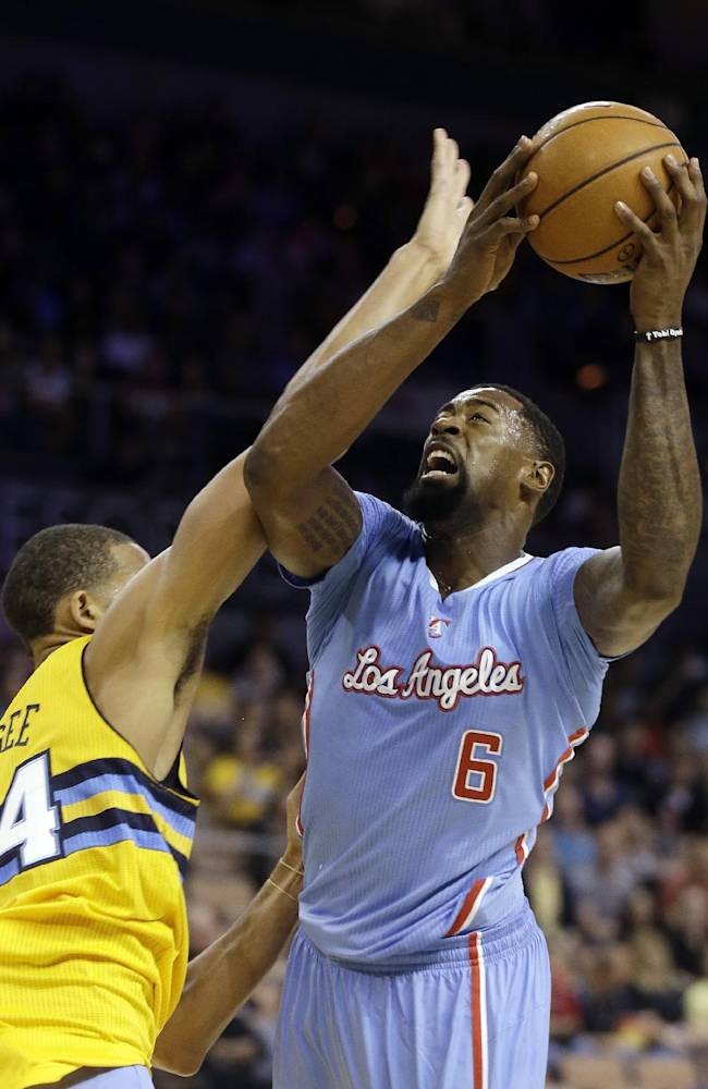 The Los Angeles Clippers' DeAndre Jordan shoots over the Denver Nuggets' JaVale McGee during the first half of a preseason NBA basketball game on Saturday, Oct. 19, 2013, in Las Vegas