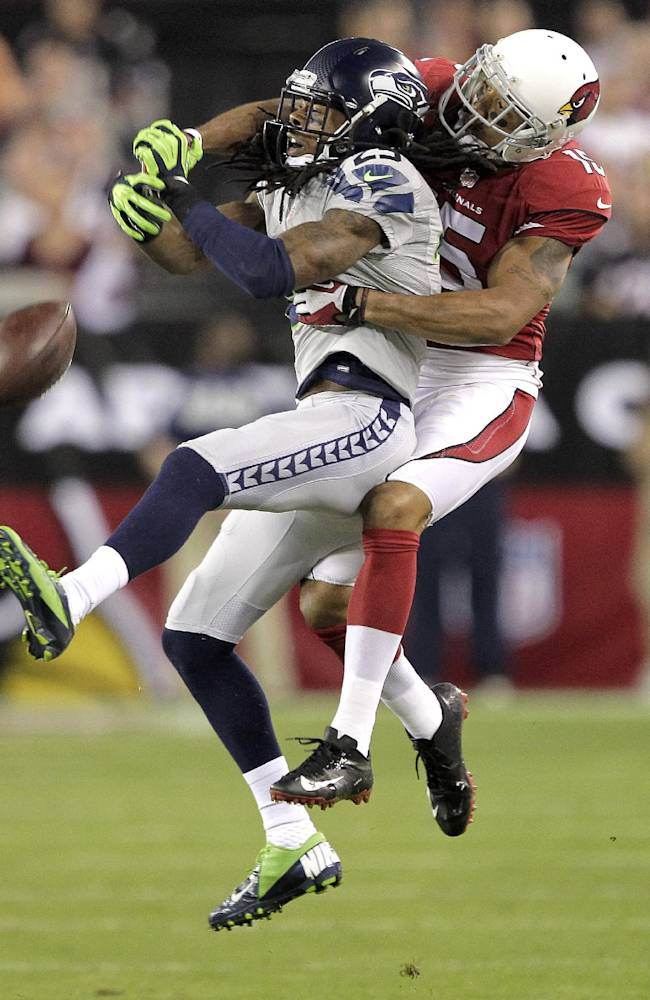 Seattle Seahawks cornerback Richard Sherman (25) breaks up a pass intended for Arizona Cardinals wide receiver Michael Floyd during the first half of an NFL football game, Thursday, Oct. 17, 2013, in Glendale, Ariz