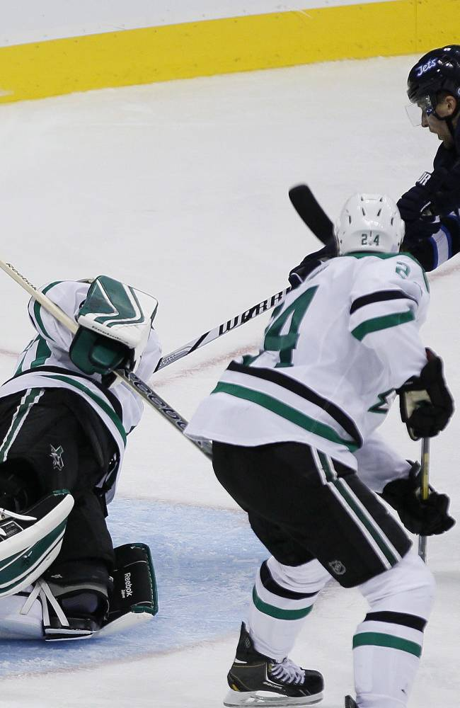 Winnipeg Jets' Blake Wheeler (26) scores the Jets' only goal against Dallas Stars' goaltender Dan Ellis, left, during third-period NHL hockey game action in Winnipeg, Manitoba, Friday, Oct. 11, 2013