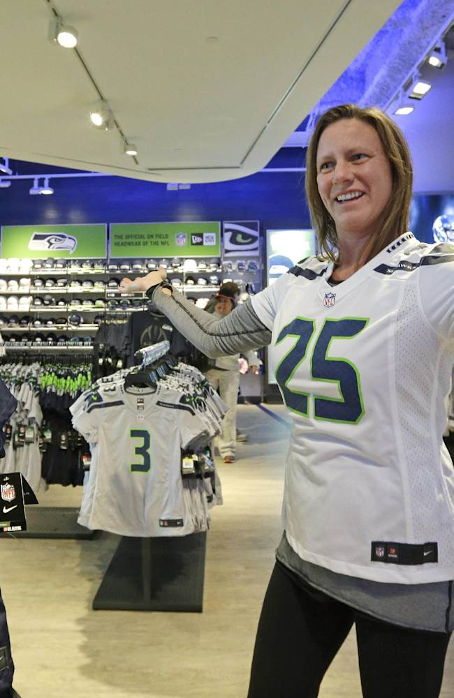 FILE- In this Jan. 13, 2014 file photo, Ellen Kelly turns to a companion to help her decide as she tries on a Seattle Seahawks' jersey at the team store in Seattle. Kelly was among a steady stream of customers making jersey, cap, sweatshirt and other Seahawks gear purchases. The same phenomenon could hold true when Super Bowl XLVIII fans converge on New York City. Instead of attending Broadway shows, seeing the New York City sights or spending money in NYC entertainment venues, the bulk of their money could flow in the direction of NFL Branded merchandise and events