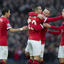 Manchester United's Robin van Persie, centre, left celebrates with teammates including Wayne Rooney, centre right, after scoring against Leicester during the English Premier League soccer match between Manchester United and Leicester at Old Trafford Stadi