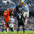 Manchester City s Alvaro Negredo, right, fights for the ball against Tottenham s Younes Kaboul, center, as Hugo Lloris, left, jumps in during their English Premier League soccer match at the Etihad Stadium, Manchester, England, Sunday Nov. 24, 2013