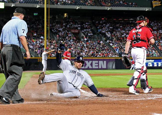 San Diego Padres' Rene Rivera scores on a sacrifice fly by Chris Denorfia as Atlanta Braves catcher Brian McCann steps away in the seventh inning of a baseball game Friday, Sept. 13, 2013, in Atlanta. The Padres won 4-3
