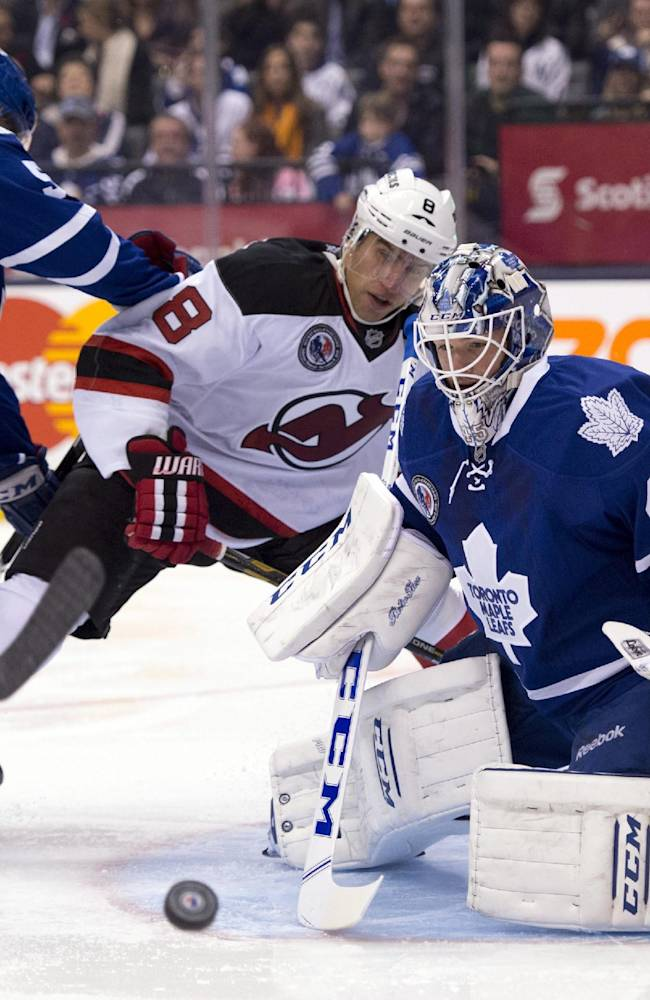 Toronto Maple Leafs defenseman Jake Gardiner checks New Jersey Devils right wing Dainius Zubrus as goalie Jonathan Bernier makes a save during the first period of an NHL hockey game, Friday, Nov. 8, 2013 in Toronto