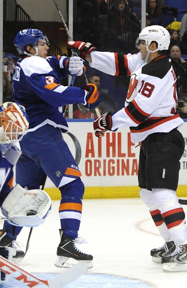 New York Islanders' Travis Hamonic (3) fights with New Jersey Devils' Steve Bernier (18) in the third period of an NHL hockey game on Saturday, March 1, 2014, in Uniondale, N.Y. The Devils won 6-1