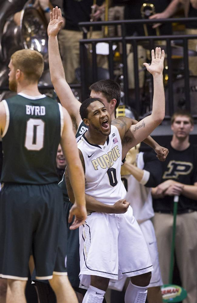 Purdue's Terone Johnson (0) reacts as his shot drops in the basket after he was fouled on the play by Michigan State's Kenny Kaminski (30) in the first half of an NCAA college basketball game, Thursday, Feb. 20, 2014, in West Lafayette, Ind