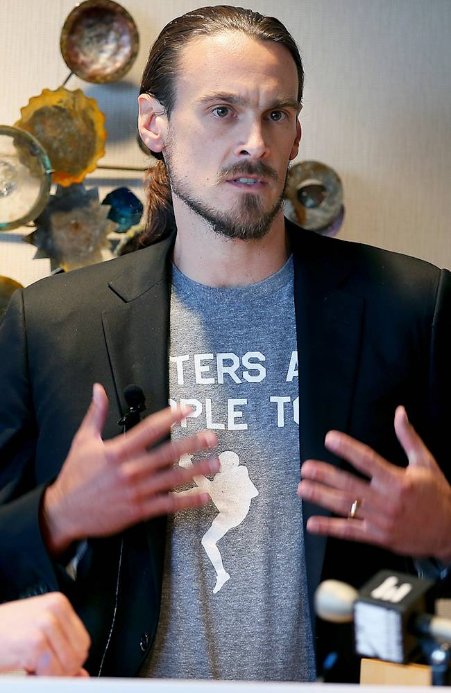 In this July 15, 2014, file photo, former Minnesota Vikings punter Chris Kluwe, right, speaks during a press conference in Minneapolis. Kluwe says he's reached a settlement with the team to avert a threatened lawsuit over his release. Kluwe had accused the Vikings of cutting him over his activism on gay rights issues. He said Tuesday, Aug. 19, 2014, that the Vikings have agreed to donate to several nonprofits to help raise awareness in professional sports about LGBT issues