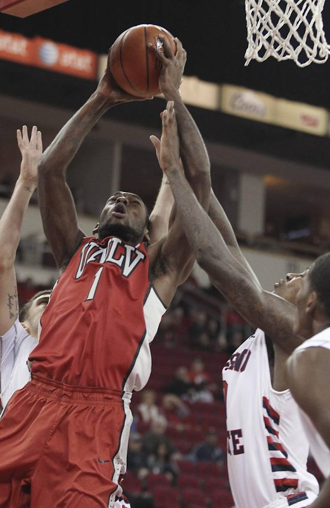UNLV's Roscoe Smith goes up against Fresno State defenders during the first half of an NCAA college basketball game in Fresno, Calif., Wednesday, Jan. 1, 2014