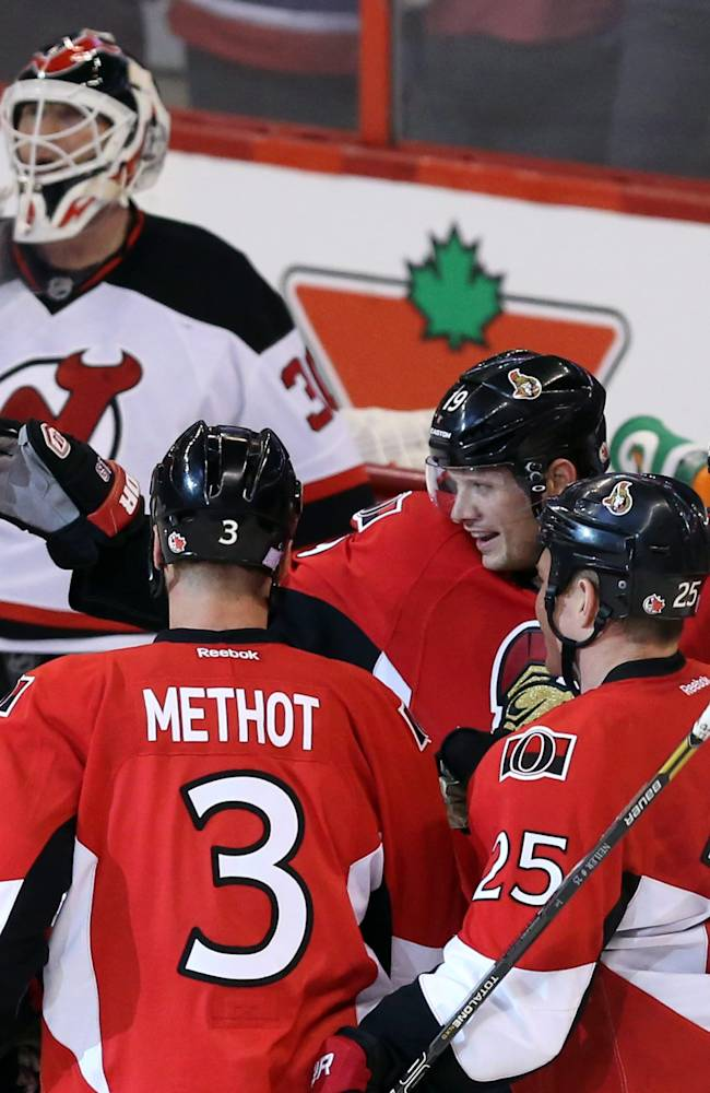 Ottawa Senators' Jason Spezza (19), Erik Karlsson (65), Marc Methot (3) and Chris Neil (25) celebrate a goal by Zack Smith, right, as New Jersey Devils goaltender Martin Brodeur looks away during the second period of an NHL hockey game Thursday, Oct. 17, 2013, in Ottawa, Ontario