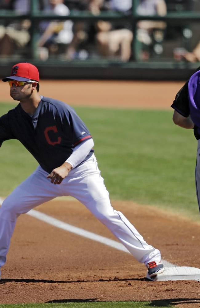 Cleveland Indians first baseman Nick Swisher takes the throw at first to get Colorado Rockies' Drew Stubbs (13) on a ground out in the first inning of a spring exhibition baseball game, Saturday, March 22, 2014, in Goodyear, Ariz