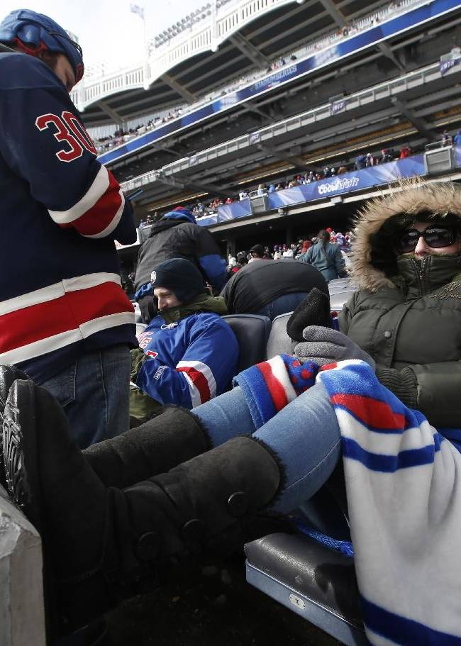 Deborah Gerth from Brookhaven, N.Y., bundles up in her seat as she waits for the start of the New Jersey Devils and New York Rangers NHL outdoor hockey game at Yankee Stadium in New York, Sunday, Jan. 26, 2014