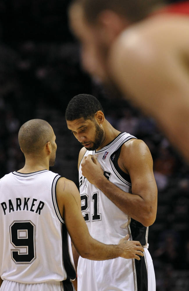 San Antonio Spurs point guard Tony Parker, left, of France, talks to Spurs forward Tim Duncan during the first half of an NBA basketball game against the Toronto Raptors, Monday, Dec. 23, 2013, in San Antonio. San Antonio won 112-99