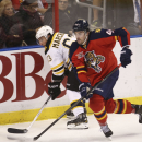 Boston Bruins' Brad Marchand (63) and Florida Panthers Eri Gudbranson (44) chase the puck during the second period of an NHL hockey game in Sunrise, Fla., Sunday, March 9, 2014 The Associated Press