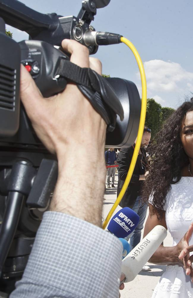 US tennis player Serena Williams, gestures as she speaks to the media after a photo call for the movie Pixels, directed by American Chris Colombus, near the Eiffel Tower, in the background, in Paris, France, Friday, May 22, 2015. Serena Williams will play at the the French Open in Paris, which starts Sunday. (AP Photo/Michel Euler)