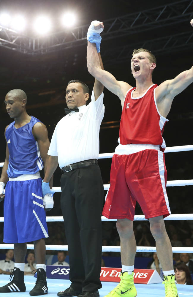 Northern Ireland's Joe Fitzpatrick, right, celebrates after defeating Lesotho's Qhobosheane Mohlerepe in their men's lightweight boxing preliminary match at the Commonwealth Games Glasgow 2014, in Scotland, Sunday, July 27, 2014