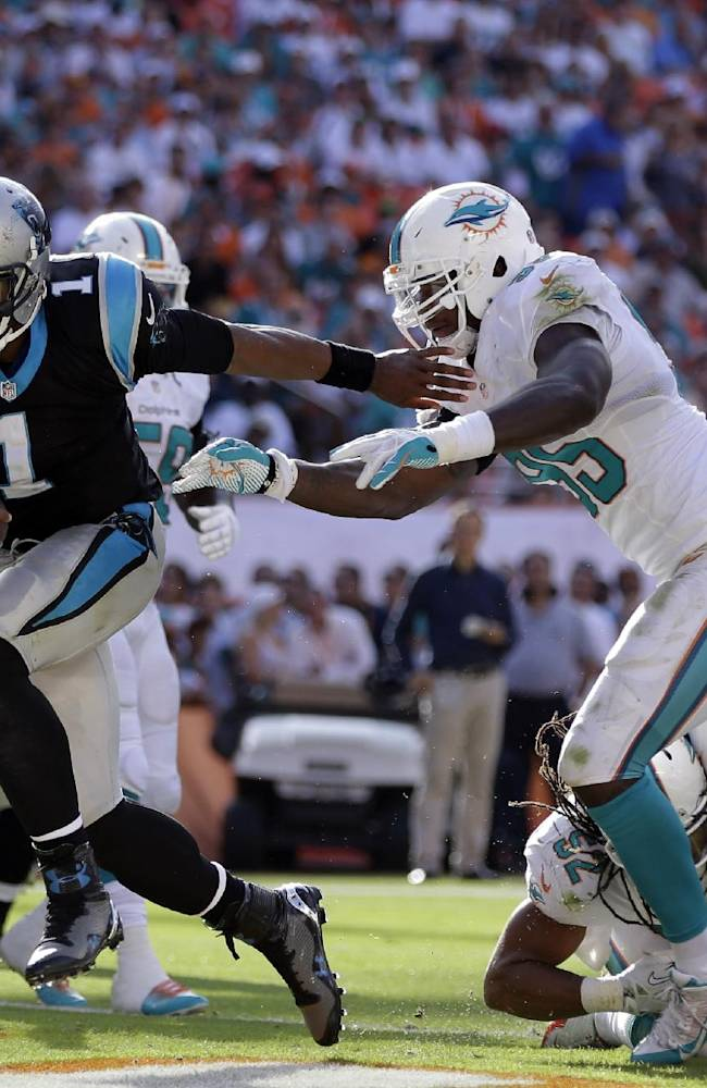 In this Nov. 24, 2013, file photo, Carolina Panthers quarterback Cam Newton (1) avoids a tackle by Miami Dolphins defensive end Dion Jordan (95) to score a touchdown during the second half of an NFL football game in Miami Gardens, Fla. The Panthers want fourth-year quarterback Cam Newton to throw more and run less as he continues to grow as an NFL quarterback. That's because they want the two-time Pro Bowler to stay healthy