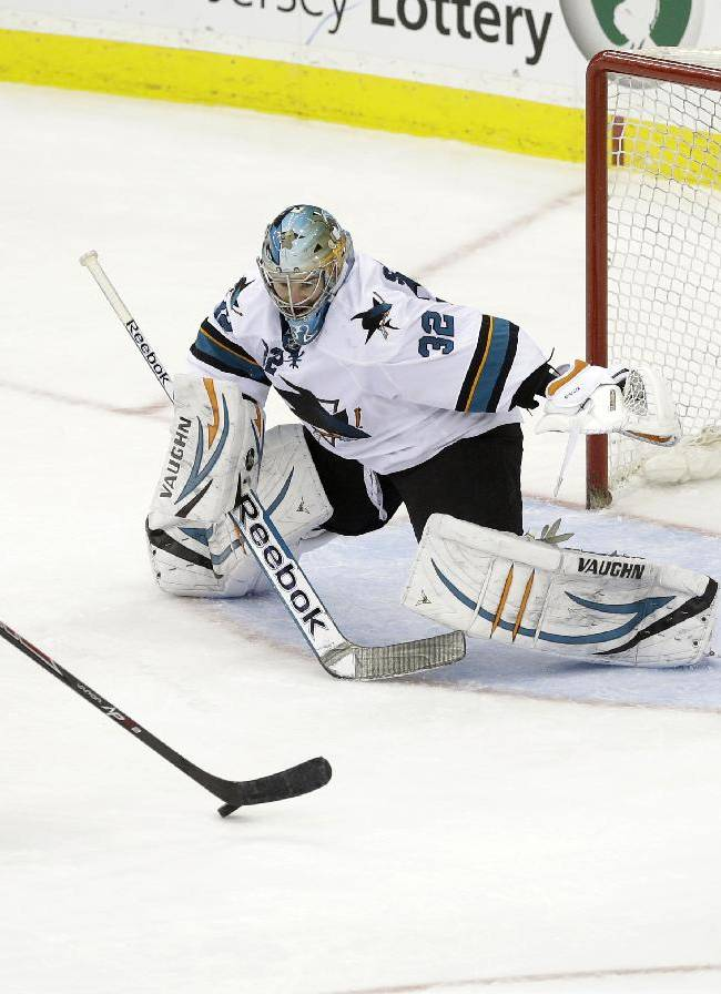 San Jose Sharks goalie Alex Stalock (32) watches the puck as New Jersey Devils' Andy Greene (6) lines up a shot during the third period of an NHL hockey game on Sunday, March. 2, 2014, in Newark, N.J. The Sharks won 4-2