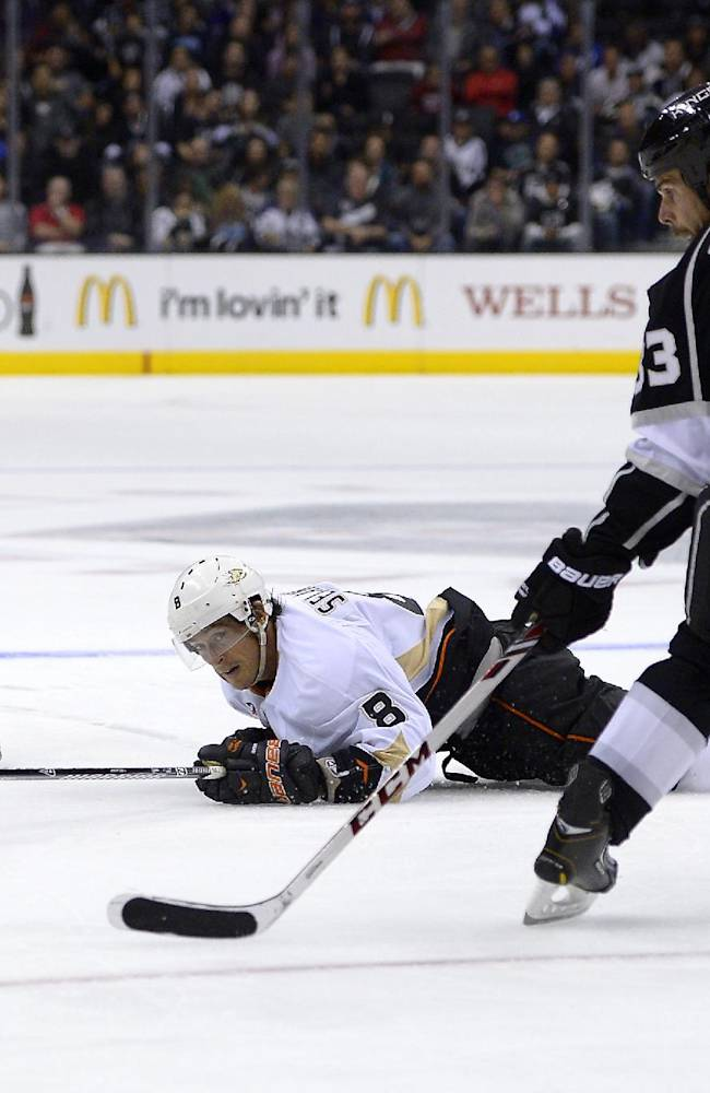 Los Angeles Kings right wing Matt Frattin, left, pass the puck to defenseman Willie Mitchell, right, as Anaheim Ducks right wing Teemu Selanne falls during the third period of their NHL preseason hockey game, Tuesday, Sept. 24, 2013, in Los Angeles. The Kings won 2-1