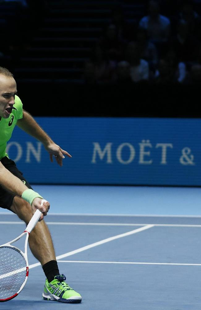 Bruno Soares of Brazil plays a return during his doubles match with Alexander Peya of Austria against against Jean-Julien Rojer of Netherlands and Horia Tecau of Romania at the ATP World Tour tennis finals at the O2 arena in London, Monday, Nov. 10, 2014