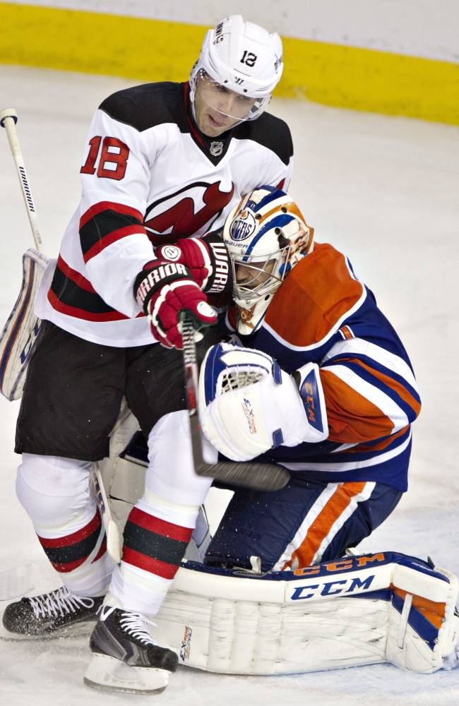 New Jersey Devils' Steve Bernier (18) runs into Edmonton Oilers goalie Jason LaBarbera (1) during the third period of an NHL hockey game Monday, Oct. 7, 2013, in Edmonton, Alberta. The Oilers won 5-4 in a shootout