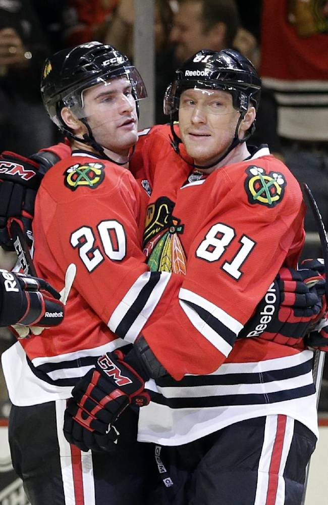 Chicago Blackhawks' Brandon Saad, left, celebrates with Marian Hossa (81) after scoring against the Tampa Bay Lightning during the second period of an NHL hockey game in Chicago, Saturday, Oct. 5, 2013