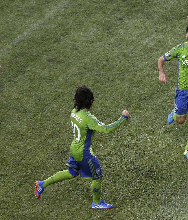 Seattle Sounders' Brad Evans, right, celebrates with Mauro Rosales, center, while New York Red Bulls' David Carney walks past after Evans scored a goal on a penalty kick in the first half of an MLS soccer match, Sunday, Sept. 29, 2013, in Seattle