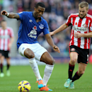 Everton's Sylvain Distin, left, vies for the ball with Sunderland's Seb Larsson, right, during their English Premier League soccer match at the Stadium of Light, Sunderland, England, Sunday, Nov. 9, 2014