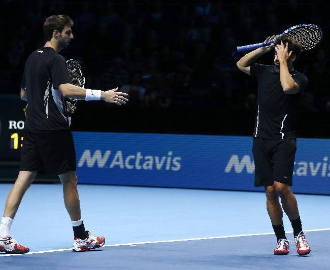 Marc Lopez of Spain, right, buries his face in his hand as Marcel Granollers of Spain looks on after loosing a point to Leander Paes of India and Radek Stepanek of Czech Republic during their ATP World Tour Finals double tennis match at the O2 Arena in London Friday, Nov. 8, 2013
