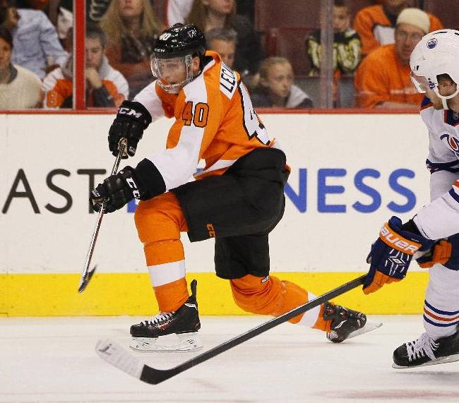 Philadelphia Flyers' Vincent Lecavalier, left, wearing a face shield, chases the puck along with Edmonton Oilers' Anton Belov, right, in the second period of an NHL hockey game, Saturday, Nov. 9, 2013, in Philadelphia