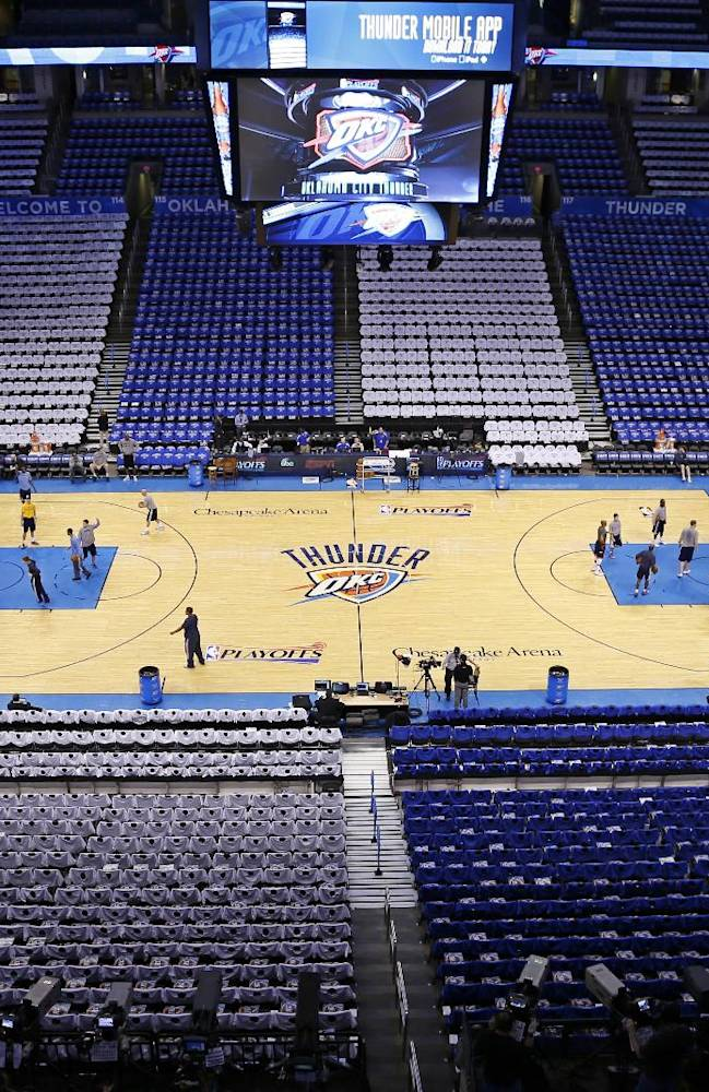 The Memphis Grizzlies and the Oklahoma City Thunder shoot around before the start of Game 2 of an opening-round NBA basketball playoff series in Oklahoma City, Monday, April 21, 2014. Alternating seating sections have chairs covered with either white or blue t-shirts for the fans