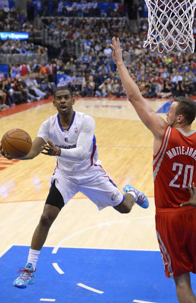 Los Angeles Clippers guard Chris Paul, left, puts up a shot as Houston Rockets forward Donatas Motiejunas, of Poland, defends during the second half of an NBA basketball game, Wednesday, Feb. 26, 2014, in Los Angeles
