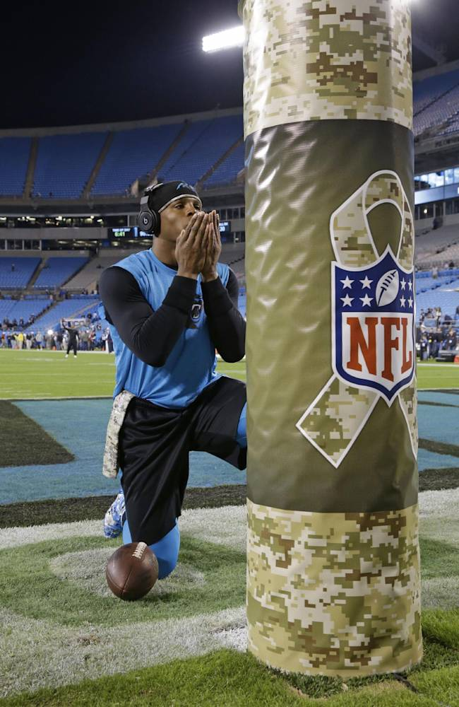 Carolina Panthers' Cam Newton (1) pauses by a goal post covered with a Salute to Service padding before an NFL football game against the New England Patriots in Charlotte, N.C., Monday, Nov. 18, 2013