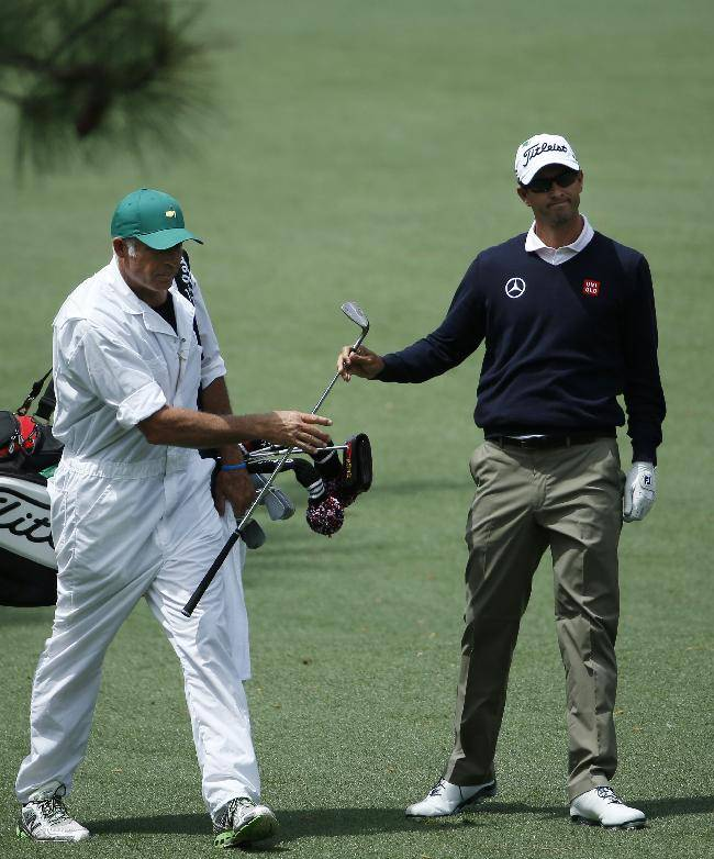 Adam Scott, of Australia, takes a club from his caddie Steve Williams on the seventh fairway during a practice round for the Masters golf tournament Tuesday, April 8, 2014, in Augusta, Ga