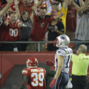 In this Sept. 29, 2014, photo, Kansas City Chiefs free safety Husain Abdullah, left, gets up in the end zone after dropping to his knees in prayer as New England Patriots wide receiver Julian Edelman, right, walks past after Abdullah intercepted a pass an