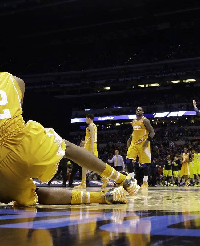 Michigan's Jordan Morgan, right, raises his arms as Tennessee's Jordan McRae gets off the floor after an NCAA Midwest Regional semifinal college basketball tournament game Friday, March 28, 2014, in Indianapolis. Michigan won 73-71