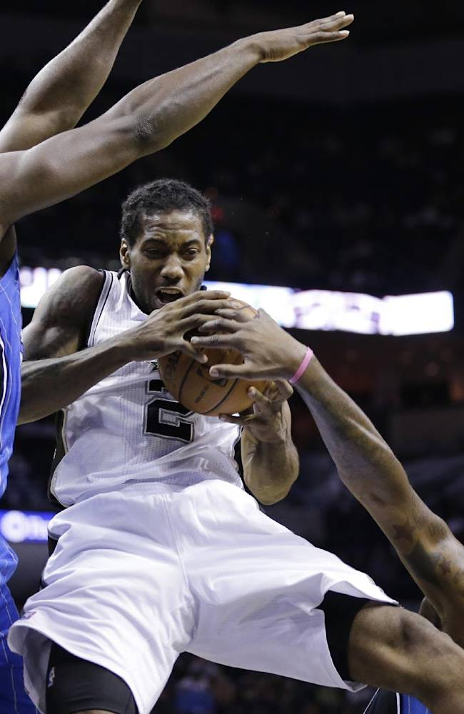 San Antonio Spurs' Kawhi Leonard (2) is defended by Orlando Magic's Jason Maxiell, left, and Kyle O'Quinn, right, during the first half of a preseason NBA basketball game, Tuesday, Oct. 22, 2013, in San Antonio