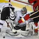 Los Angeles Kings goalie Jonathan Quick, centre, keeps his eyes on the uck as teammate Drew Doughty, left, and Calgary Flames' Joe Colborne crash into him during third period NHL hockey action in Calgary, Alberta, on Thursday Feb. 27, 2014 The Associated