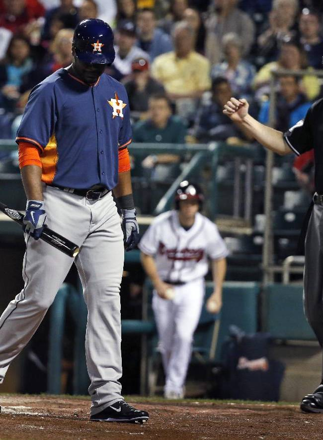 Home plate umpire Seth Buckminster signals the strike-out on Houston Astros' Chris Carter in the third inning of a spring exhibition baseball game against the Atlanta Braves, Friday, Feb. 28, 2014, in Kissimmee, Fla. The Astros won 7-5