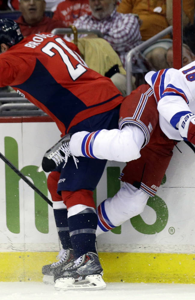 Washington Capitals right wing Troy Brouwer, left, boards New York Rangers defenseman Marc Staal in the first period of an NHL hockey game, Wednesday, Oct. 16, 2013, in Washington