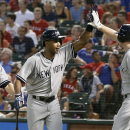 New York Yankees' Chris Young is congratulated by Brendan Ryan, right, after Young hit a grand slam against the Texas Rangers in the third inning of a baseball game Tuesday, July 28, 2015, in Arlington, Texas. The shot that came off of Rangers reliever Wandy Rodriguez scored Alex Rodriguez, Mark Teixeira and Brett Gardner, left rear. (AP Photo/Tony Gutierrez)