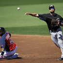 Colorado Rockies shortstop Paul Janish throws over Cleveland Indians' Carlos Santana to complete a double play on Indians' Michael Brantley in the second inning of a spring exhibition baseball game, Saturday, March 22, 2014, in Goodyear, Ariz The Associa