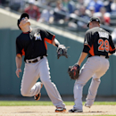 Miami Marlins second baseman Jeff Baker, left, and first baseman Greg Dobbs chase after a popup from Atlanta Braves' Freddie Freeman during the sixth inning of a spring exhibition baseball game in Kissimmee, Fla., Wednesday, March 26, 2014 The Associated